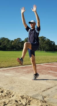 An image demonstrating a long jump take-off position with arms extended above the head.