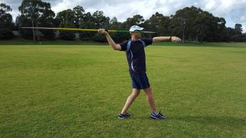 Right-handed javelin thrower standing with right foot forward - side view