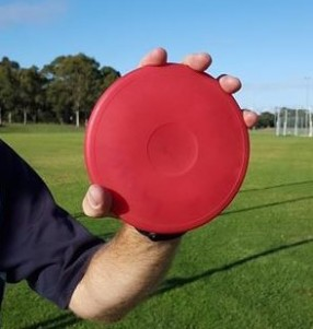 Discus held with thumb incorrectly over the edge.