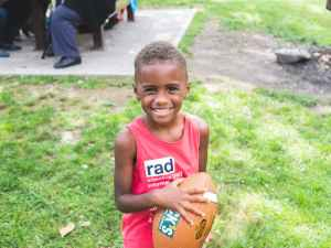 boy wears red tank top holding football ball